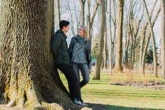 Piękna kochająca para uśmiecha się wielkiego drzewa w parku i całuje Obrazy Stock