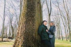 Piękna kochająca para uśmiecha się wielkiego drzewa w parku i całuje Zdjęcia Stock