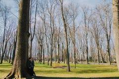 Piękna kochająca para uśmiecha się wielkiego drzewa w parku i całuje Zdjęcie Royalty Free
