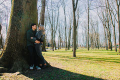 Piękna kochająca para uśmiecha się wielkiego drzewa w parku i całuje Zdjęcia Royalty Free