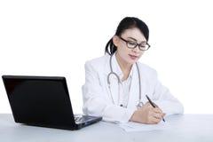 Piękna lekarka pisze recepcie - odosobnionej zdjęcie stock