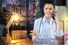 Piękna lekarka używa gesty podczas gdy opowiadający na telefonie Zdjęcia Stock