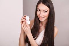 Piękna, ludzi, kosmetyków, skincare i zdrowie pojęcie, - szczęśliwa uśmiechnięta młoda kobieta stosuje śmietankę jej twarz Fotografia Royalty Free
