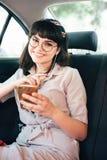 Piękna młoda ładna dziewczyna używa mądrze telefon i ono uśmiecha się podczas gdy siedzący na tylnym siedzeniu w samochodzie zdjęcie stock