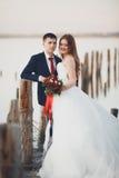Piękna młoda ślub para, państwo młodzi pozuje blisko drewnianych słupów na tła morzu Obraz Royalty Free
