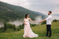 Piękna młoda ślub pary pozycja na zielonym skłonie, wzgórze Fornal i panna młoda w Karpackich górach obraz royalty free