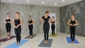 Piękna młoda żeńska leżanka stojąca wyjaśnia oddychania joga ćwiczenie, ćwiczy podczas gdy Zdjęcia Stock