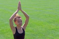 Piękna młoda afroamerykańska kobieta w czarnej koszulce zamykał ona oczy i podnosi ona up przeciw tłu ręki zdjęcie stock