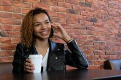 Piękna młoda afroamerykańska kobieta w kurtce z białego papieru szkłem w jeden ręce siedzi przy stołem i ono uśmiecha się, podcza zdjęcia royalty free