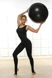 Piękna młoda atrakcyjna piękna kobieta trzyma up piłkę dla sprawności fizycznej czerni z blondyn pozycją ubierał up w czarnym kos Obraz Royalty Free