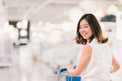 Piękna młoda Azjatycka kobieta uśmiecha się, z wózek na zakupy, centrum handlowego lub wydziałowego sklepu sceną, plamy bokeh tło Obrazy Stock