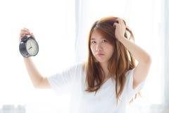 Piękna młoda azjatykcia kobieta budził się w ranki dokuczających alarmowych clo obraz royalty free
