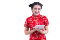 Piękna Młoda azjatykcia kobieta jest ubranym chińczyka smokingowego tradycyjnego cheongsam qipao lub Ręki trzyma laptop i używa Fotografia Stock