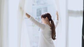 Piękna młoda azjatykcia kobieta z szczęśliwymi otwartymi zasłonami i rozciągliwość gnuśna przy okno po budzimy się ranek w sypial zbiory