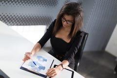 Piękna młoda biznesowa dama w czarnym silnym apartamencie siedzi przy biurowym stołem Fotografia Stock