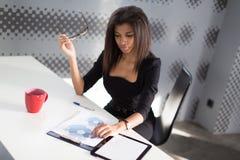 Piękna młoda biznesowa dama w czarnym silnym apartamencie siedzi przy biurowym stołem Zdjęcia Royalty Free