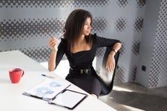 Piękna młoda biznesowa dama w czarnym silnym apartamencie siedzi przy biurowym stołem Zdjęcie Stock