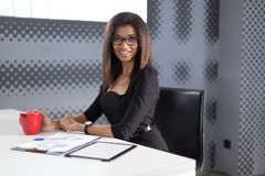 Piękna młoda biznesowa dama w czarnym silnym apartamencie siedzi przy biurowym stołem, chwyt czerwieni filiżanka Obraz Royalty Free