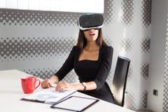 Piękna młoda biznesowa dama w czarnym silnym apartamencie siedzi przy biurowym stołem w vr szkłach Zdjęcie Stock