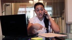 Piękna młoda biznesowa dziewczyna opowiada na telefonie komórkowym dyskutuje biznesowego projekt w biurowym obsiadaniu przy stołe zbiory wideo
