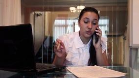 Piękna młoda biznesowa dziewczyna opowiada na telefonie komórkowym dyskutuje biznesowego projekt w dokumentach w biurowym obsiada zbiory