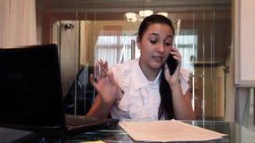 Piękna młoda biznesowa dziewczyna opowiada na telefonie komórkowym dyskutuje biznesowego projekt w dokumentach w biurowym obsiada zbiory wideo