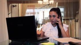 Piękna młoda biznesowa dziewczyna opowiada na telefonie komórkowym w biurowym obsiadaniu przy stołem zdjęcie wideo
