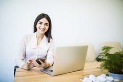 Piękna młoda biznesowa kobieta używa smartphone i ono uśmiecha się podczas gdy pracujący w nowożytnym biurze Obraz Stock