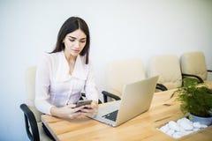 Piękna młoda biznesowa kobieta używa smartphone i ono uśmiecha się podczas gdy pracujący w nowożytnym biurze Zdjęcie Stock