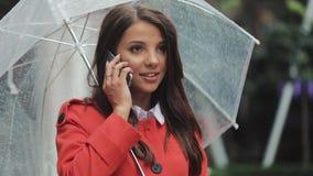 Piękna młoda biznesowa kobieta używa smartphone na ulicie w dżdżystej pogodzie, ono uśmiecha się, trzymający parasol, wybiera num zbiory