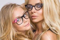 Piękna młoda blond seksowna mama urocza mała dziewczynka z długie włosy w czarnych szkłach snuggling obiektyw na a i patrzeje Fotografia Stock