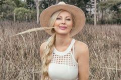 Piękna młoda blondynka w kapeluszu pozuje w polu ucho obrazy royalty free
