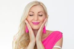 Piękna młoda blondynka z zamkniętymi oczami i uśmiechem, trzyma ręki twarzą Emocje błogość i przyjemność fotografia royalty free