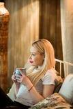 Piękna młoda blondynki dziewczyna relaksuje z filiżanką Obraz Royalty Free
