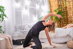 Piękna młoda blondynki kobieta, rozciąga mięśnie jej plecy i ręki, wykonuje gimnastycznych ćwiczenia w domu z bezpłatnym tekstem obraz stock