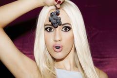 Piękna młoda blondynki kobieta z czystą skórą z winogronami w jego Fotografia Stock