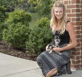 Piękna młoda blondynki kobieta z jej uroczym małym psem zdjęcia stock
