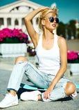 Piękna młoda blondynu modela dziewczyna w lato modnisiu odziewa z deskorolka Zdjęcie Royalty Free