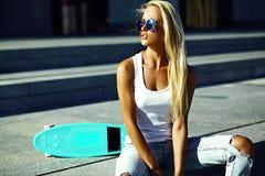 Piękna młoda blondynu modela dziewczyna w lato modnisiu odziewa z deskorolka Fotografia Royalty Free