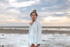 Piękna młoda boho stylu dziewczyna na plaży przy zmierzchem potomstwa na obraz stock