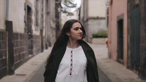 Piękna młoda brązowowłosa kobieta z długie włosy spacerami zestrzela wąską grodzką ulicę swobodny ruch zbiory
