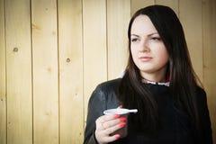 Piękna młoda brunetka pije od plastikowej filiżanki Zdjęcie Royalty Free