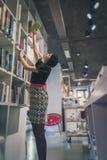 Piękna młoda brunetka pozuje w bookstore Zdjęcie Royalty Free