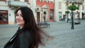 Piękna młoda brunetki dziewczyna ono uśmiecha się wiruje przed kamerą i jej włosy poci się i wiruje w wiatrze ProRes zbiory