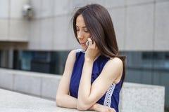Piękna młoda brunetki kobieta dzwoni telefonem Fotografia Stock