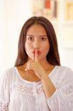 Piękna młoda brunetki kobieta jest ubranym białego bluzka wierzchołek, nakrywkowy usta używać palec, okładzinowa kamera, jaskrawy obraz stock
