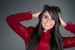 Piękna młoda brunetki kobieta jest ubranym czerwoną skórzaną kurtkę Zdjęcia Royalty Free