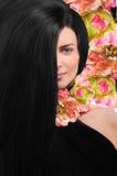 Piękna młoda brunetki kobieta na różowym kwiecistym tle obrazy royalty free
