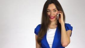 Piękna młoda brunetki kobieta opowiada na jej telefonie komórkowym zbiory