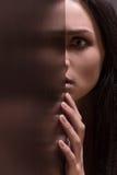 Piękna młoda brunetki kobieta patrzeje okaleczający zdjęcia stock
